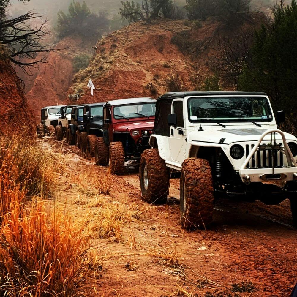 Row of buggies and ATVs on an off road trip